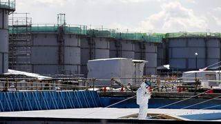 En arbeider står foran tanker fylt med radioaktivt vann ved Fukushima DaiIchi kjernekraftverk. I dag er det ti år siden ulykken.