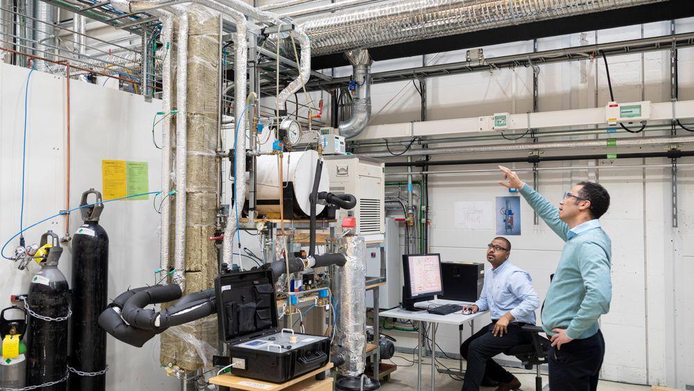 Sintef-forskernes løsning for CO2-fangst er blitt mye mer effektiv – og med det også billigere for industrien. Her er forsker Abdelghafour Zaabout (t.h) og PhD-student ved NTNU, Chaitanya Dhoke i laben foran demonstratoren.