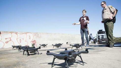 to personer ser på mange droner som står på bakken. Sondre Andreas Engebråten til venstre.