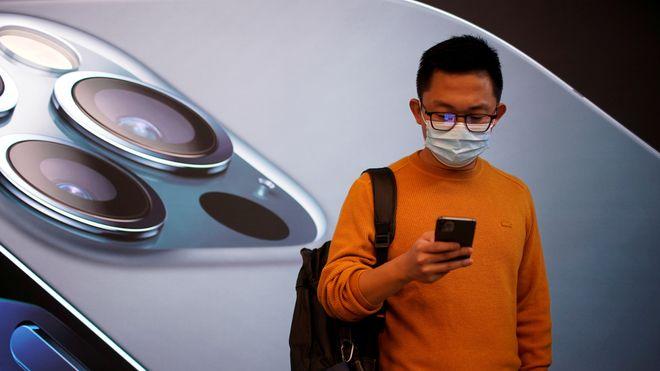 En mann bærer ansiktsmaske mens han venter i en Apple Store i Shanghai, Kina ved lansering av Iphone 12 i fjor høst.