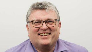 Lars Olav Grøvik smiler med lilla skjorte og briller