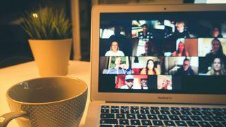 Foto av skjermmøte på Mac med kaffekopp og plante ved siden av