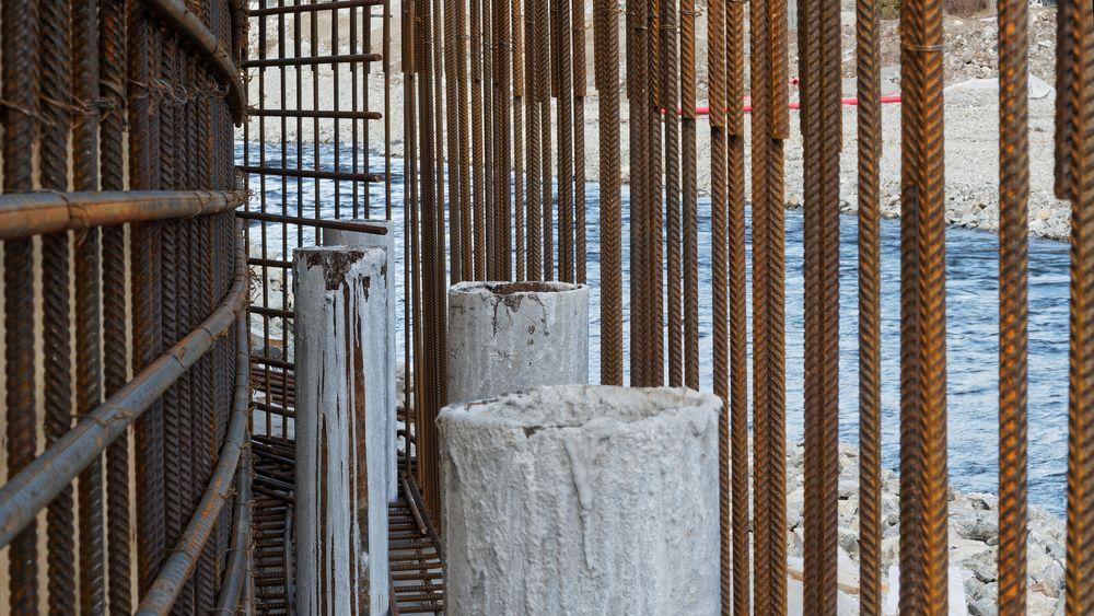 Enkelte steder er lite plass mellom eksisterende bygg og elveløpet, som her. Da må det bygges en solig mur, pelene er boret minimum to meter ned i solid fjell, og forankrer muren som etter hvert blir støpt.
