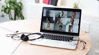 en pc med et videomøte på skjermen, briller og øretelefoner lagt delvis oppå tastaturet