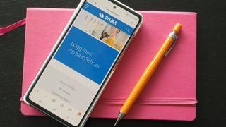 en smartelefon ligger på en rosa bok og viser påloggingssiden til Visma InSchool