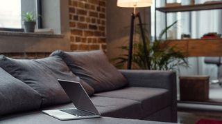 En laptop ligger på sofaen i en stue.