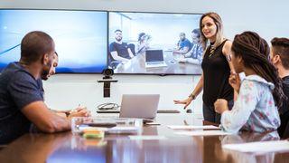 Kollegaer diskuterer ssamtidig som de deltar i en videokonferanse i et møterom.