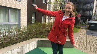 Balanserer på line på en lekeplass i rød jakke