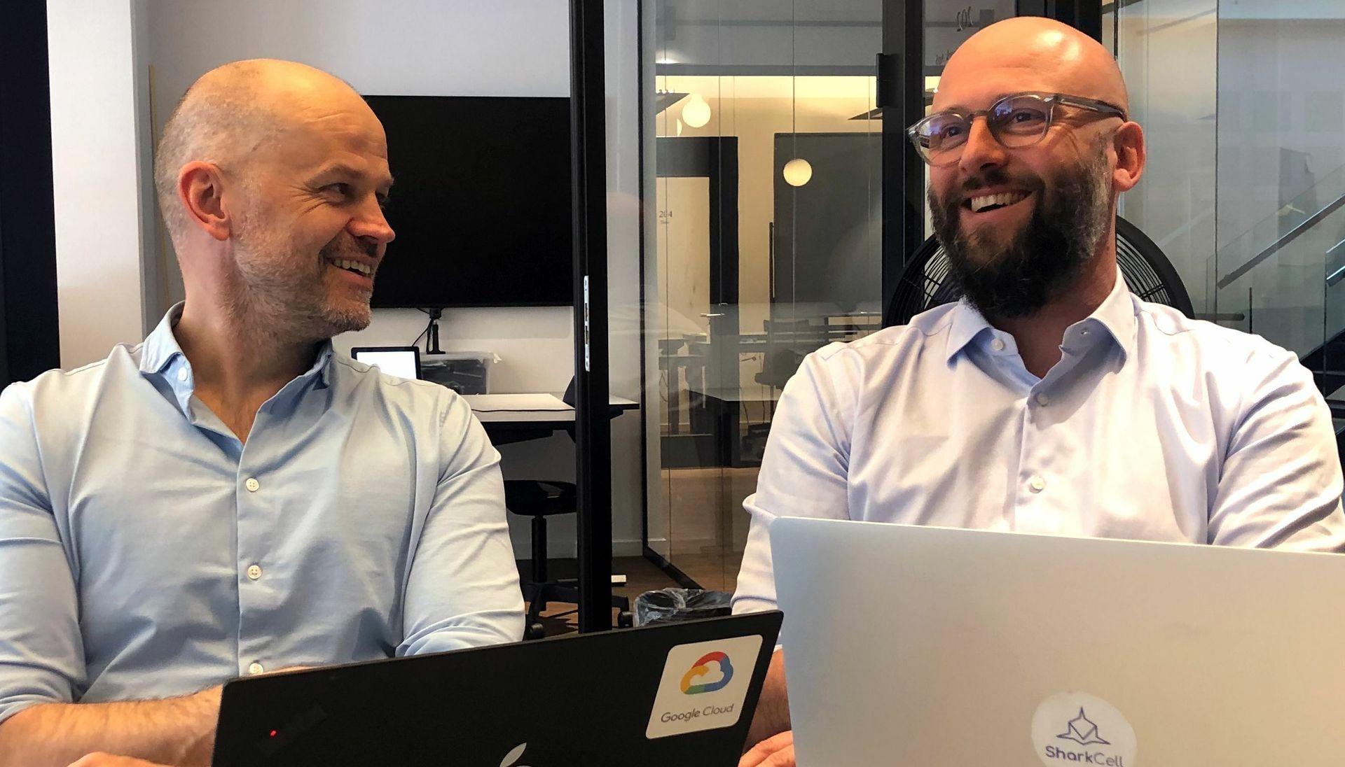 Daglig leder i Computas Danmark Jon-Gunnar Aasen (t.v.) og administrerende direktør i SharkCell Frederik Brøns feirer sammenslåingen. Foto: Computas