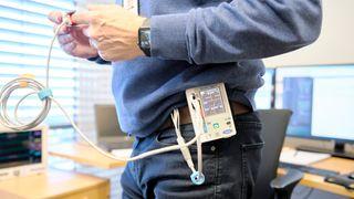 Den lille bærbare monitoren festes til kroppen og er koblet til elektroder på kroppen for å registrere hjerterytme og syv andre parametre. Den registrerer de samme data som en sykehusmonitor. En slik kan såvidt ses til venstre i bildet.