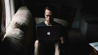 Mann med mac i sofa. Mørkt