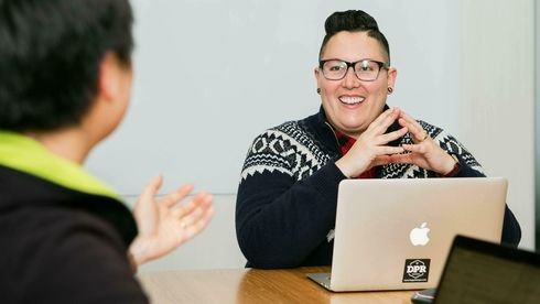 To personer med pc/mac snakker sammen. Kvinne med briller, kvinne med svart hår sees delvis bakfra.
