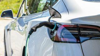 Tesla Model 3 lader med ladestasjon og Type 2-kontakt.