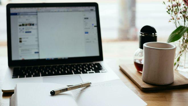 PC-skjerm, bok, penn og kaffekopp.