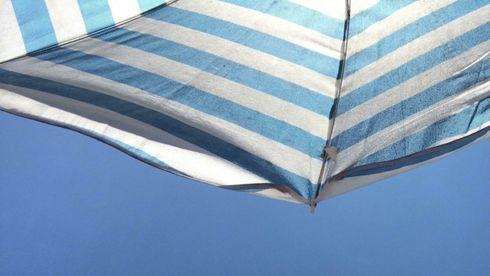 Blå himmel og bit av blå- og hvitstripete parasoll.