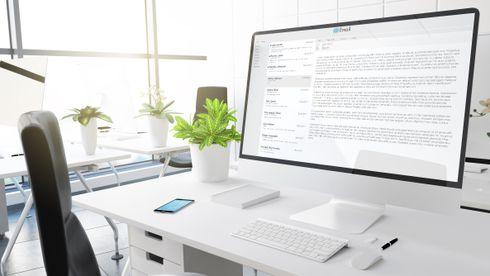 En kontorpult med en stor skjerm som viser en e-post-konto