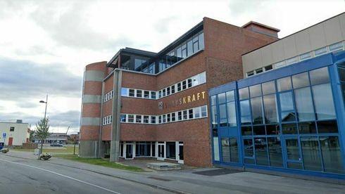 Forblåst nord-norsk gate med statlig bygg fra 80-tallet i brun murstein med blått stål.