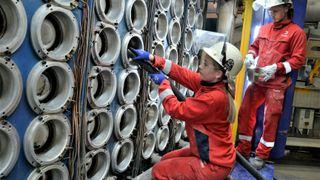 Det kreves stor nøyaktighet og grundighet under tilrigging før støping av aluminiumbolter. Her er Sara Lemicka Brix og Jonatan Espeland i gang med å støvsuge åpningene i støpebordet før nytt metall kan fylles i.