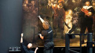 To museumsarbeidere henger opp en av de nye kantene til bildet Nattevakten av Rembrandt