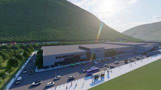 stort industribygg med to grønne fjell bak