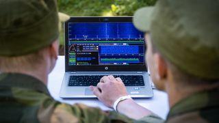 Denne uken har forsvarets fremtidige cyberingeniører opptak. Her jobber to kandidater med en spektrumsanalysator.