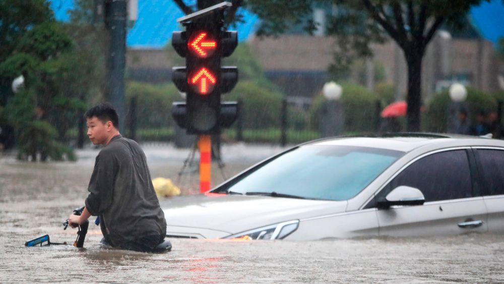 En mann forsøker å komme seg fram på sykkel gjennom vannmassene i Zhengzhou i det sentrale Kina.