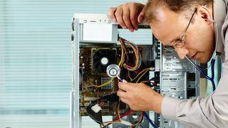 Dataingeniør som undersøker en stasjonær datamaskin med stetoskop.