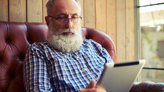 Eldre herre sitter med tablet hjemme.