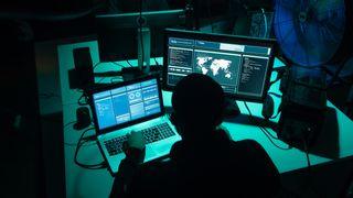 To hackere sitter i mørket foran PC-er.