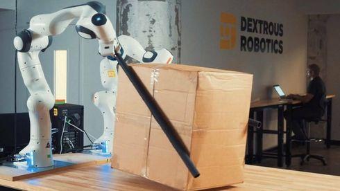 """Robot holder en pakke ved hjelp av """"spisepinner""""."""