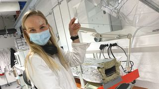 Ph. D-stipendiat på NTNU, Silje Nornes Bryntesen, viser hvordan hun kan måle energi-effektiviteten i batteriproduksjonen i en selvlaget «tørkeovn» på det nye batterilaboratoriet på Gløshaugen.