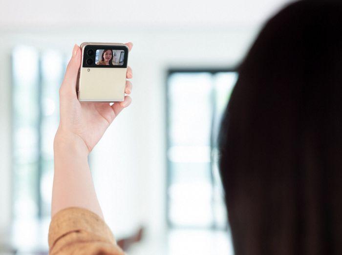 Kvinne tar selfie med lukket klapptelefon