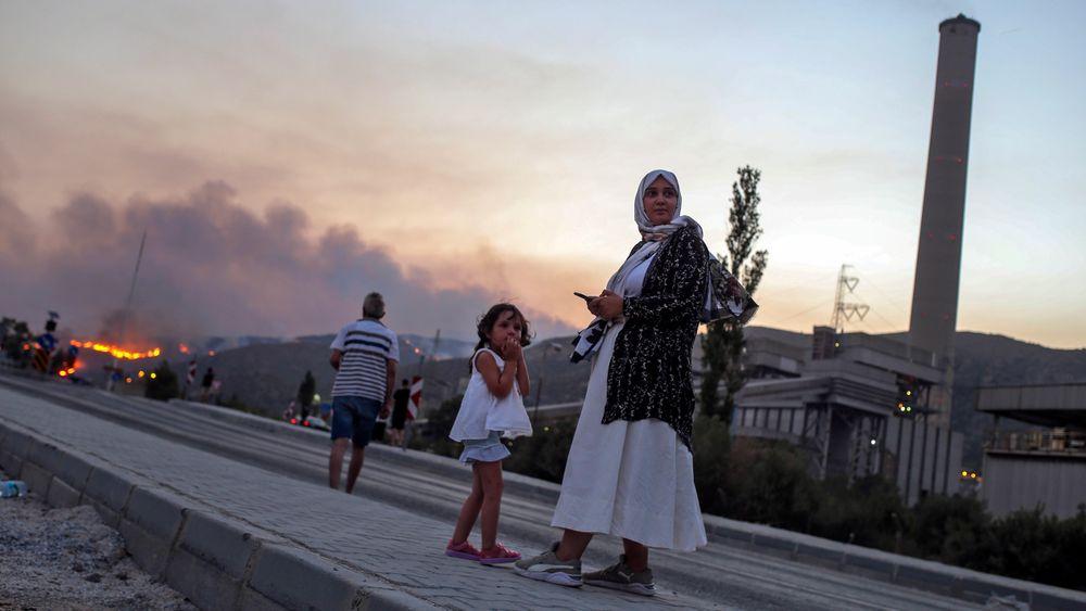 Skogbrannene i Tyrkia har drevet mange innbyggere på flukt. Bildet er fra kraftverket i Kemerkoy, med skogbrannen som nærmer seg i bakgrunnen.
