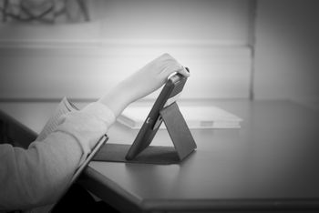 Student som leser og trykker på en iPad
