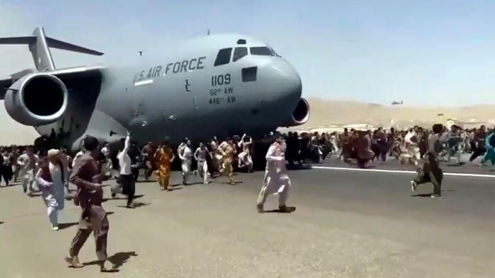 Hundrevis av mennesker springer rundt og klamrer seg fast til et C-17 som takser på flyplassen i Kabul mandag.
