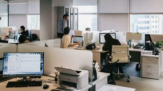 Illustrasjonsfoto av mennesker som sitter og står i kontorlandskap med hvite pulter og utsikt til høye bygninger.