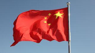 Kinesisk flagg som vaier foran blå himmel