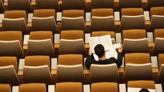 En mannlig student sitter alene i forelesningssal sett bakfra