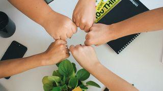 Fem personer holder hver sin hånd i en ring over kontorstæsj.