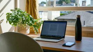 Skrivebord foran vindu med gul gardin, laptop, vannflaske og telefon.