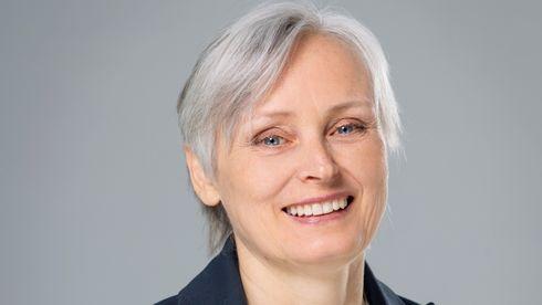 Smilende kvinne i dressjakke og hvit bluse, kort grått hår.