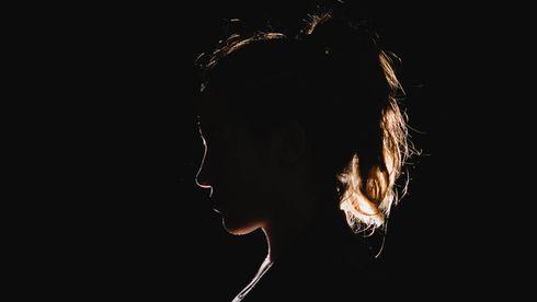 Ung kvinne med hestehale i profil - motlys - svart bakgrunn
