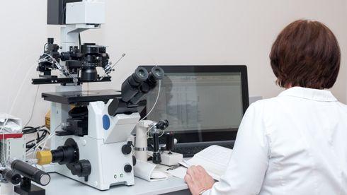 EN kvinne i hvit frakk sitter med ryggen til oss foran et mikroskop og en pc