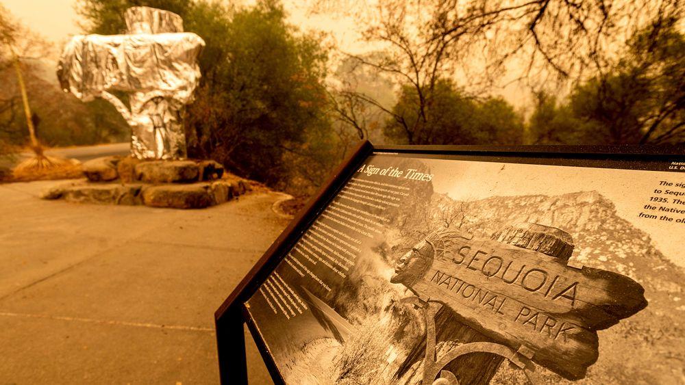 Et historisk «velkommen»-skilt er pakket inn i brannresistent folie i Sequoia National Park i California, som er hjem til verdens største sequoia-trær. Nå er også flere av trærne pakket inn.