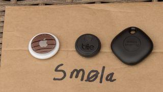 Sporingbrikker fra Apple, Tile og Samsung på toppen av en posekonvolutt som det er skrevet «Smøla» på.