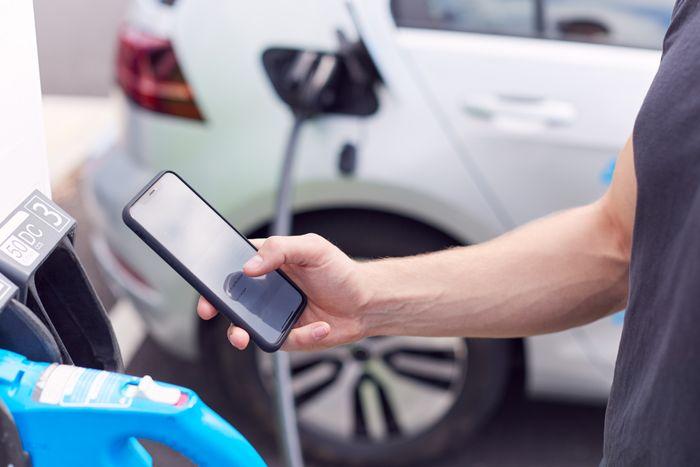man leser på mobilen mens bilen lades.