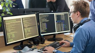 En ung mann sitter ved datamaskinen og programmerer