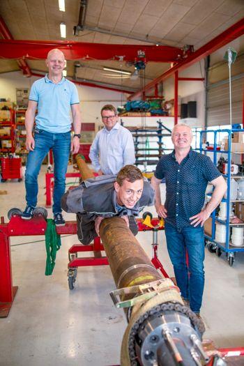 Fire menn står og ler.