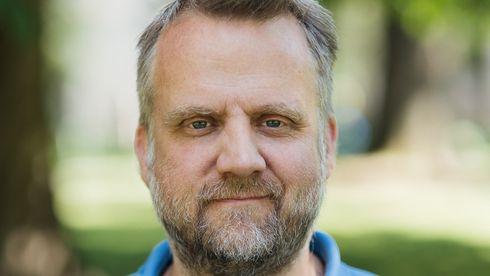 Mann med skjegg i blå piquetskjorte ute om sommeren