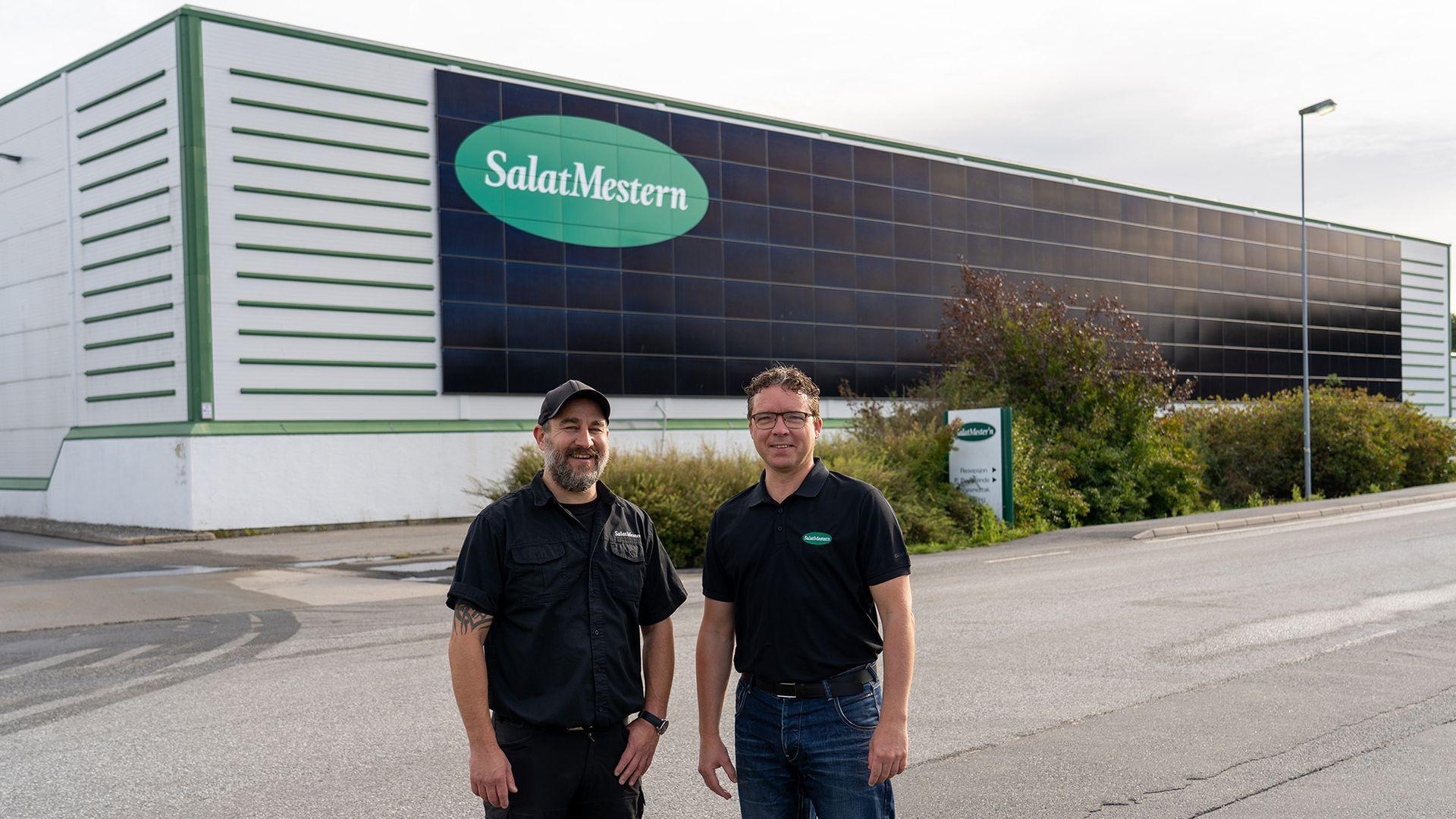 Vedlikeholdsleder Ketil Heie og kvalitetsleder Jan Børge Aune foran fabrikken til Salatmestern. Dette er det største fasadeanlegget med standardpaneler som Solcellespesialisten har montert.